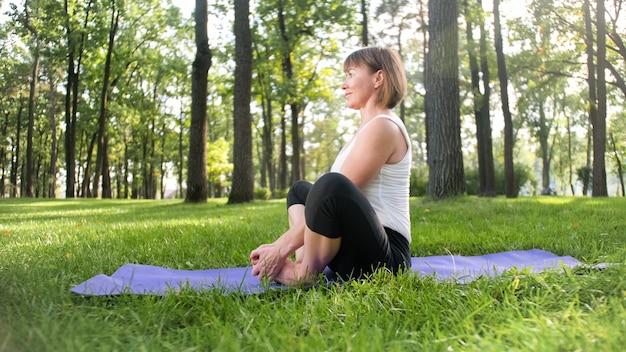 Foto van een glimlachende vrouw van middelbare leeftijd die yoga asana beoefent. persoon mediteren in de natuur. balans en harmonie van lichaam en geest