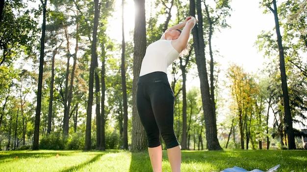 Foto van een glimlachende vrouw van middelbare leeftijd die yoga beoefent en mediteert in het park. vrouw die zich uitstrekt en fitness doet op de mat in het bos