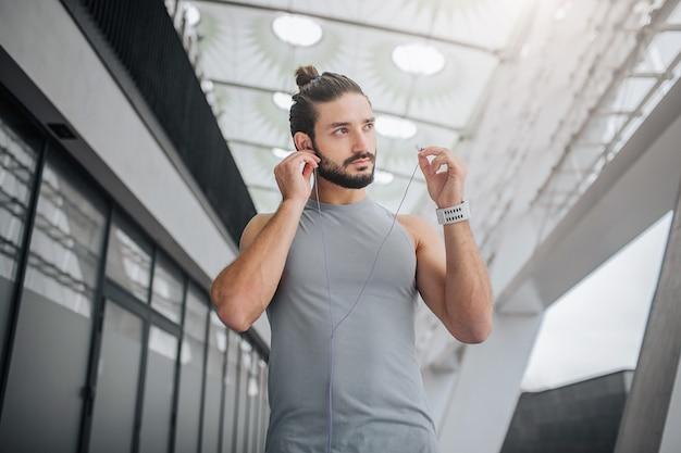 Foto van een goedgebouwde en knappe bebaarde jonge man kijkt naar rechts. hij stopt een koptelefoon in de oren. guy loopt op stadion. hij is alleen.