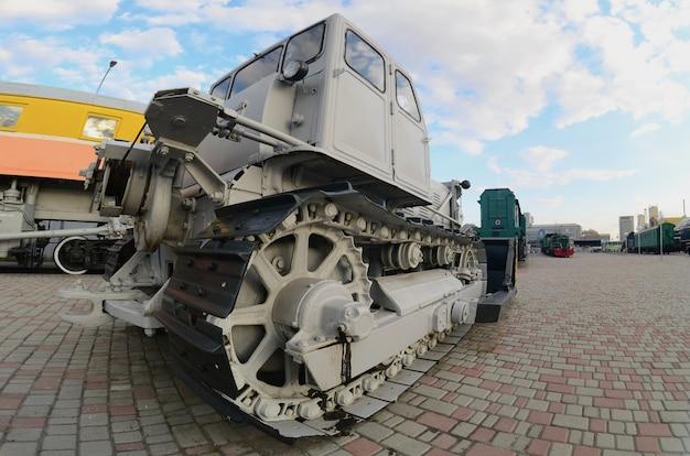 Foto van een grijze bulldozer onder de spoorwegtreinen. sterke vervorming van de fisheye-lens