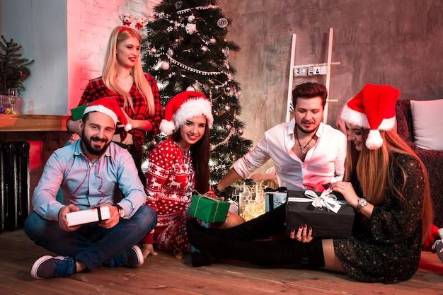 Foto van een groep vrienden met kerstcadeautjes op een feestje thuis