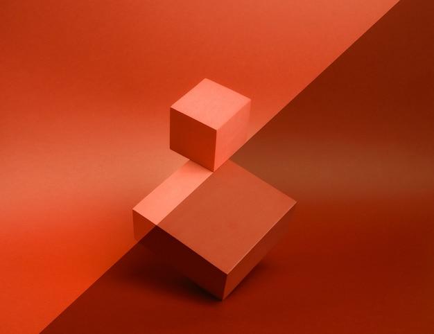 Foto van een helder podium (voetstuk) van twee kubussen op een papieren achtergrond.