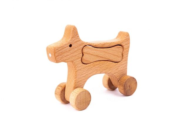 Foto van een houten hond met been op wielen van beuk.