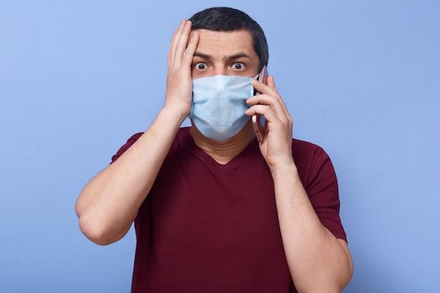 Foto van een hulpeloze, verwarde, zwartharige man, in masker, telefonerend, telefonisch pratend, geschokte gezichtsuitdrukking, hand op gezicht gelegd, bang voor coronavirus. paniek concept.