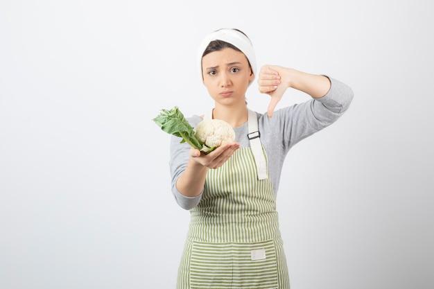 Foto van een jong aardig vrouwenmodel in schort met een bloemkool met een duim omlaag