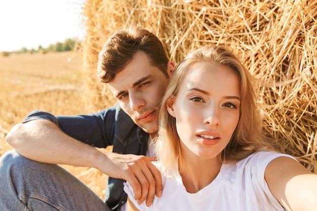 Foto van een jong koppel man en vrouw die selfie zittend onder grote hooiberg in gouden veld, tijdens zonnige dag