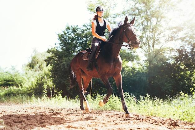 Foto van een jong mooi meisje dat haar paard in de natuur berijdt