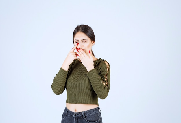 Foto van een jong mooi vrouwenmodel dat haar mond bedekt van hoest.