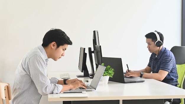 Foto van een jong programmeursteam terwijl ze aan het werk zijn / zich concentreren op het werk op kantoor.