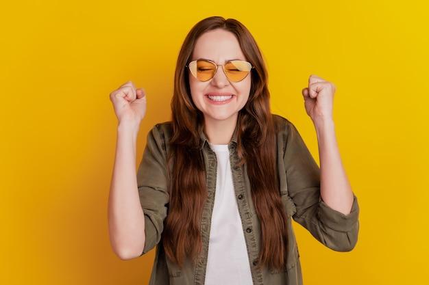 Foto van een jong vrolijk meisje vraagt smeek om vuisten vast te houden in overwinning geïsoleerd op gele achtergrond