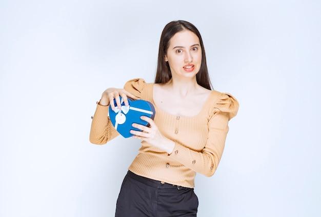 Foto van een jong vrouwenmodel dat een blauwe giftdoos houdt tegen witte muur.
