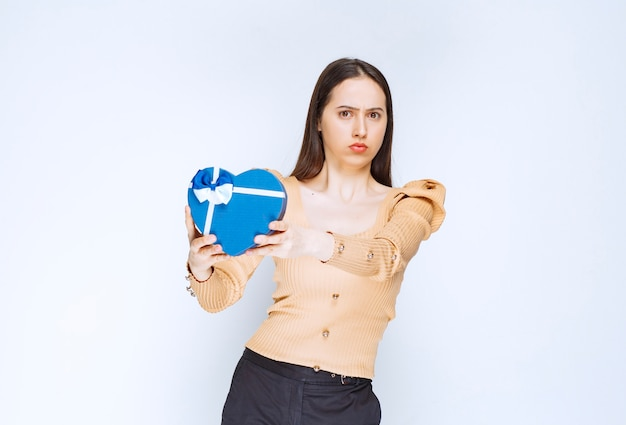 Foto van een jong vrouwenmodel dat een hartvormige giftdoos houdt tegen witte muur.