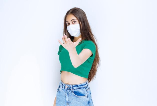 Foto van een jong vrouwenmodel dat staat en een beschermend medisch masker draagt.