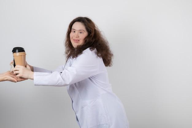 Foto van een jong vrouwenmodel in wit uniform dat een kopje koffie geeft.