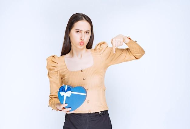 Foto van een jong vrouwenmodel met een hartvormige geschenkdoos die naar beneden wijst.
