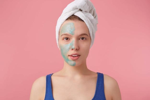 Foto van een jonge aardige dame met een handdoek op haar hoofd na het douchen, een masker op de vloer zetten om het effect te vergelijken, kijkt naar stands