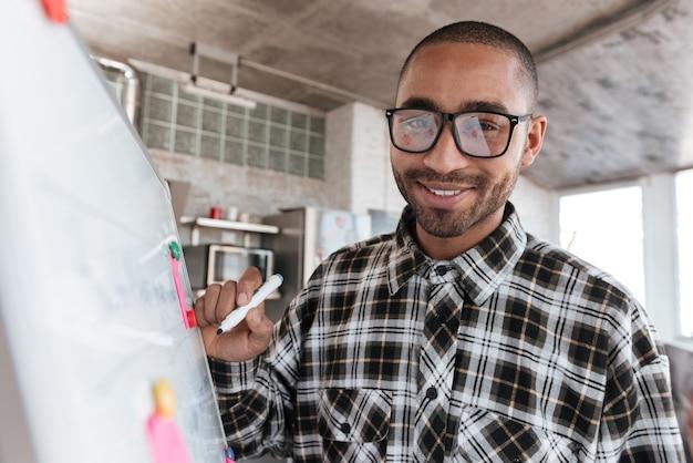 Foto van een jonge afrikaanse vrolijke zakenman met een bril in kantoor die met flip-over werkt. kijk naar de camera.