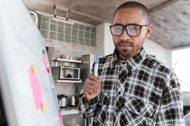 Foto van een jonge afrikaanse zakenman met een bril in kantoor die met flipchart werkt. kijk op flipover.