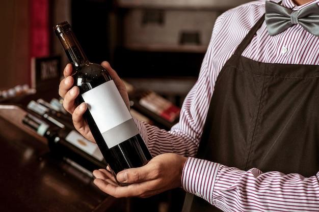 Foto van een jonge barman die in zijn handen een dure fles elitewijn toont