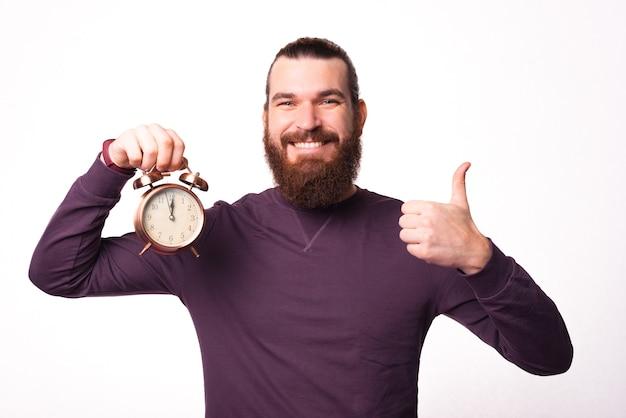 Foto van een jonge, bebaarde man die een klok vasthoudt en een duim toont