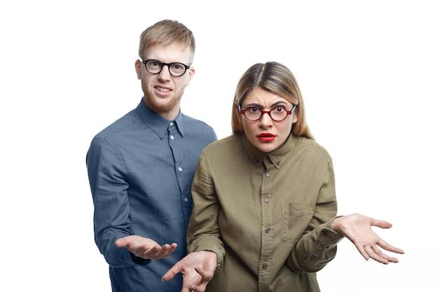 Foto van een jonge, bebaarde man en blonde vrouw die allebei een bril dragen en staan en hun verontwaardiging uiten, schouderophalend en hulpeloos gebaar maken, omdat ze geen idee hebben wat er aan de hand is