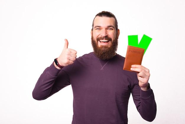 Foto van een jonge bebaarde man met een paspoort met twee kaartjes erin vertoont een duim omhoog en glimlacht