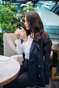 Foto van een jonge blanke vrouw drinkt warme koffie of thee in het café voor de harde werkdag