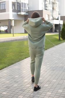 Foto van een jonge blanke vrouw in een groen sportpak en zwarte sneakers staat terug naar de camera en houdt een kap