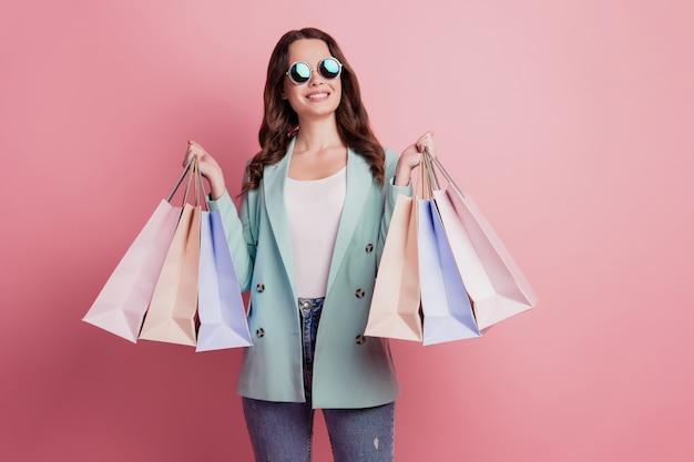 Foto van een jonge brunette vrouw met winkelpakketten die zich voordeed op een roze muur, ziet er lege ruimte uit