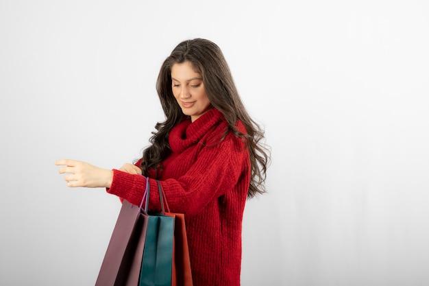 Foto van een jonge dame die naar haar kleurrijke boodschappentassen kijkt.