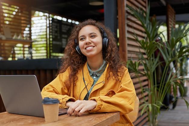 Foto van een jonge donkerhuidige, krullende studentendame die op een caféterras zit, naar muziek luistert en dromerig wegkijkt, in een gele jas draagt, koffie drinkt, werkt op een laptop.