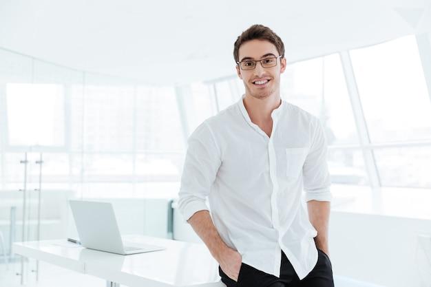 Foto van een jonge gelukkige man gekleed in een wit overhemd dat over een grote witte raamachtergrond staat camera kijken.