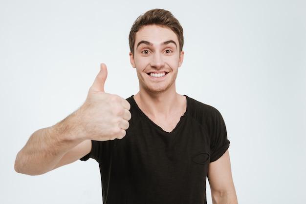 Foto van een jonge gelukkige man gekleed in een zwart t-shirt dat over een witte achtergrond staat en naar de camera kijkt en een duim omhoog gebaar toont.