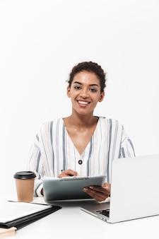 Foto van een jonge geschokte mooie afrikaanse vrouw die zich voordeed over een witte muur met behulp van een laptopcomputer met klembord.