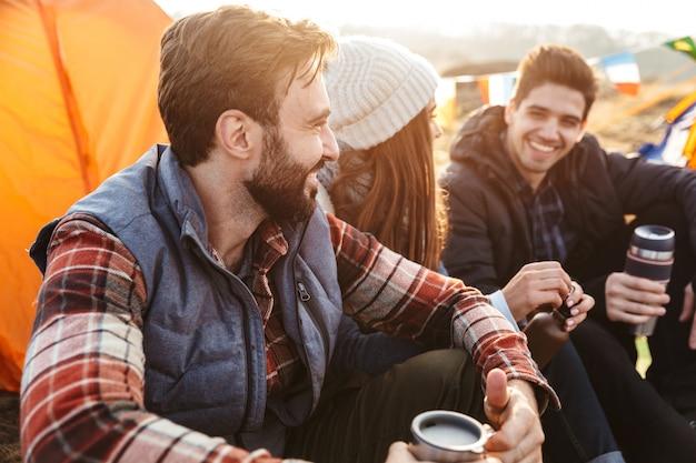 Foto van een jonge groep vrienden buiten op een gratis alternatieve vakantiecamping boven de bergen die hete thee drinken terwijl ze met elkaar praten.