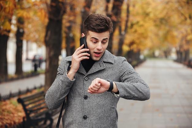 Foto van een jonge kerel die op smartmobile spreekt terwijl hij op zijn horloge kijkt en te laat is