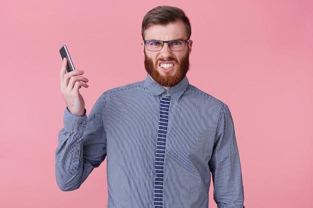 Foto van een jonge knappe bebaarde man met een bril en een gestreept overhemd, die de telefoon van zijn oor af houdt, omdat hij wordt gebeld door een woedende baas die een telefoon uitrust. geïsoleerd op roze achtergrond.