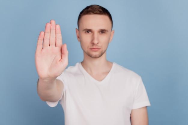Foto van een jonge, knappe man, ongelukkig, verdrietig, toon geen stopbord, weigeren, weigeren, geïsoleerd op een blauwe achtergrondkleur