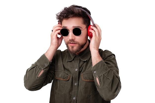 Foto van een jonge man die een zonnebril draagt en muziek luistert op een koptelefoon op een witte achtergrond
