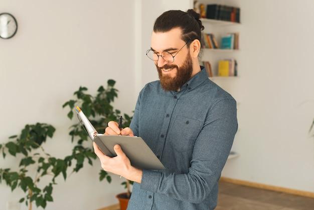 Foto van een jonge man die in zijn kantoor zit en in een planner schrijft