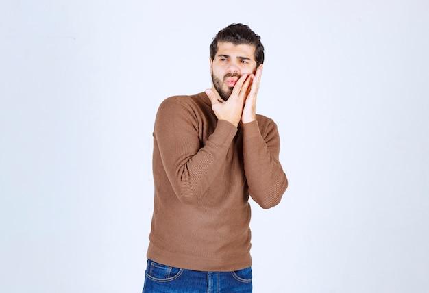 Foto van een jonge man die staat en zijn wang aanraakt