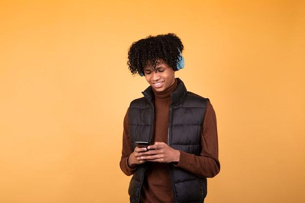 Foto van een jonge man in een donker vest met telefoon, vrienden chatten, moderne muziektechnologie met blauwe koptelefoon. geïsoleerde afbeelding op gele achtergrond.