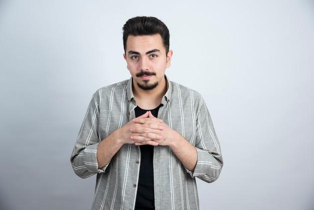 Foto van een jonge man in vrijetijdskleding die zich over witte muur bevindt.