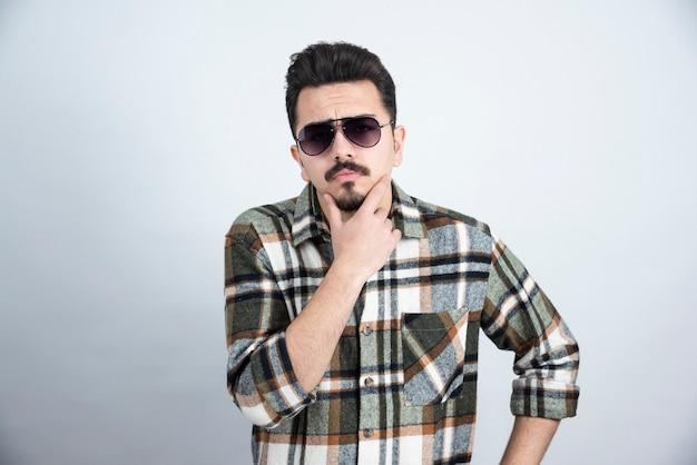 Foto van een jonge man in zwarte glazen staande op een witte muur.
