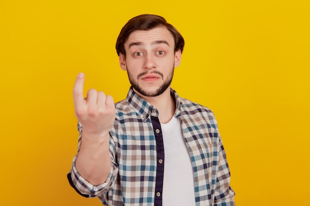 Foto van een jonge man laat de vinger zien en nodig een symboolconflict uit dat geïsoleerd is over een gele kleurachtergrond