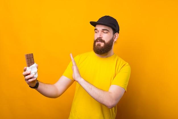 Foto van een jonge man met baard die nee zegt tegen chocolade
