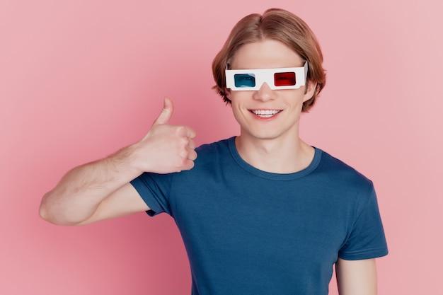 Foto van een jonge man met een 3d-bril, kijk naar de film, laat de duim omhoog zien als een coole advertentie, geïsoleerd op een pastelkleurige achtergrond