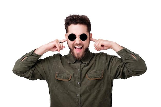 Foto van een jonge man met een baard die een zonnebril draagt en vingers in de oren steekt voor minder lawaai