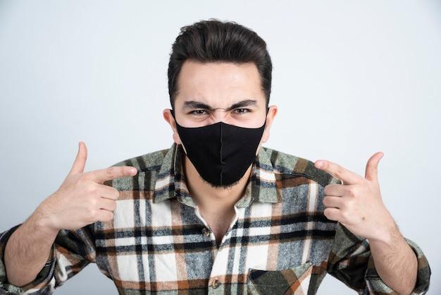 Foto van een jonge man met een zwart masker voor bescherming op een witte muur.