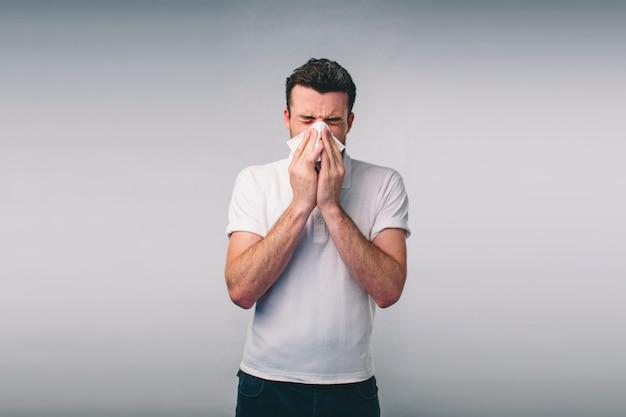 Foto van een jonge man met zakdoek. de zieke geïsoleerde kerel heeft loopneus. man geneest een verkoudheid. nerd draagt een bril